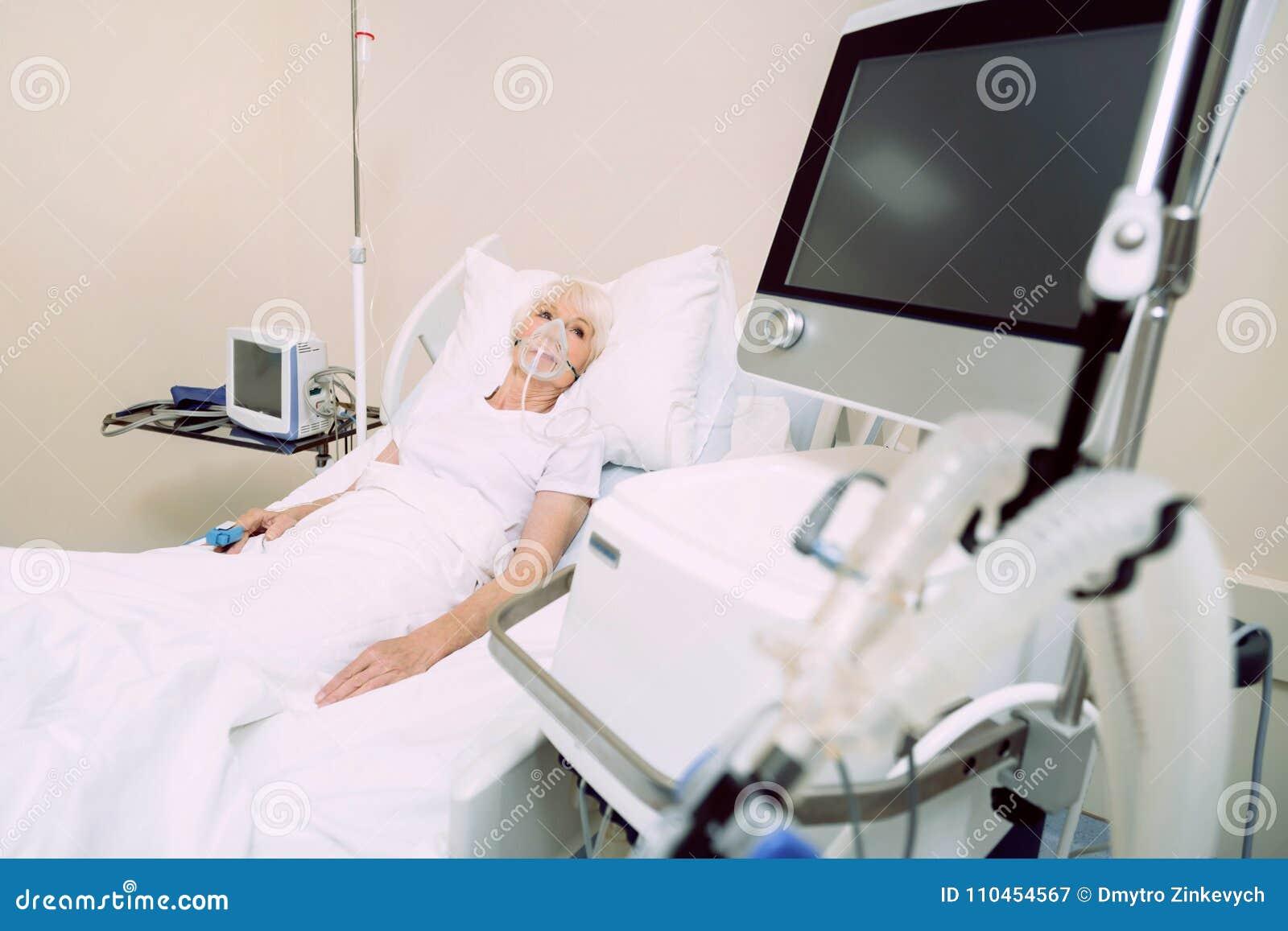 Dåligt kvinna med medicinsk utrustning för hjärtahastighet som ser bildskärmen