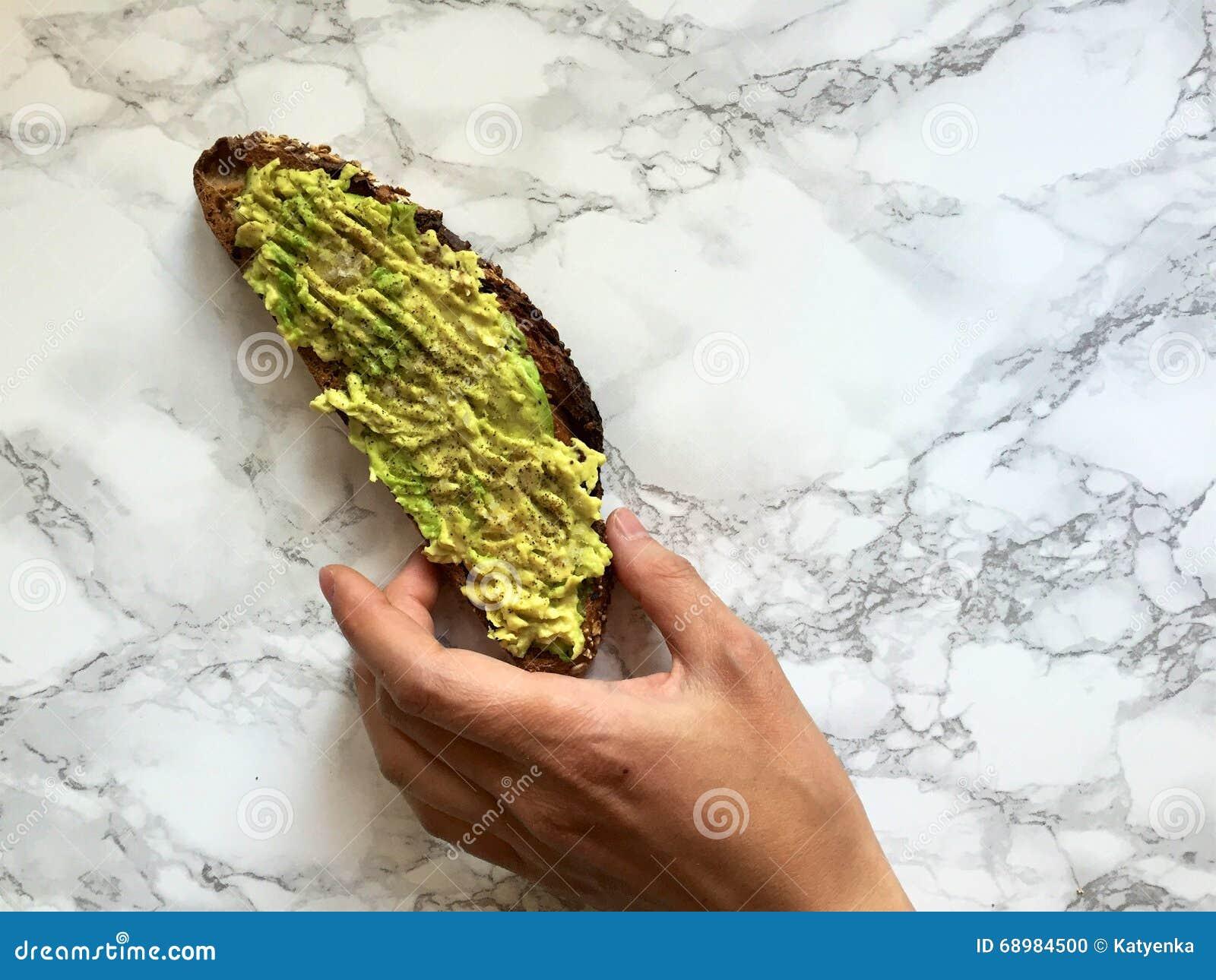 Dé alcanzar para la tostada entera artesanal del grano con el aguacate y la sal del mar