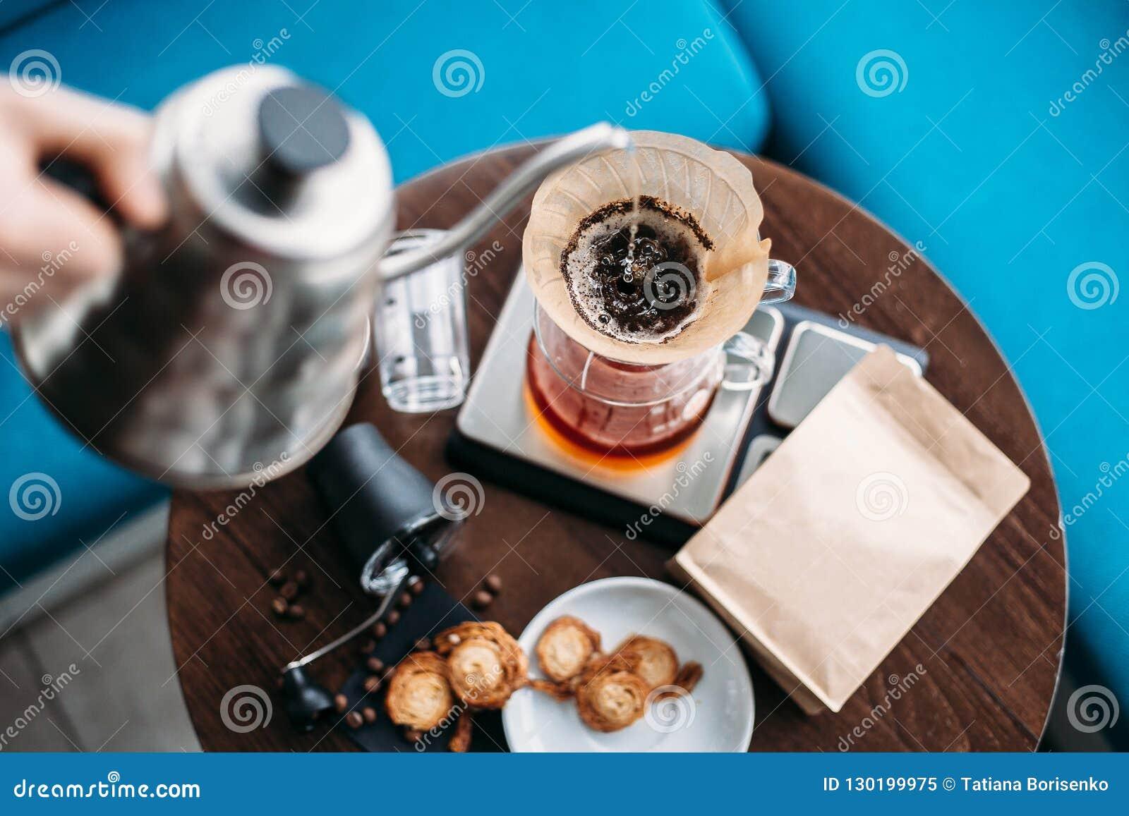 Dé el café del goteo, agua de colada de Barista en poso con el fi