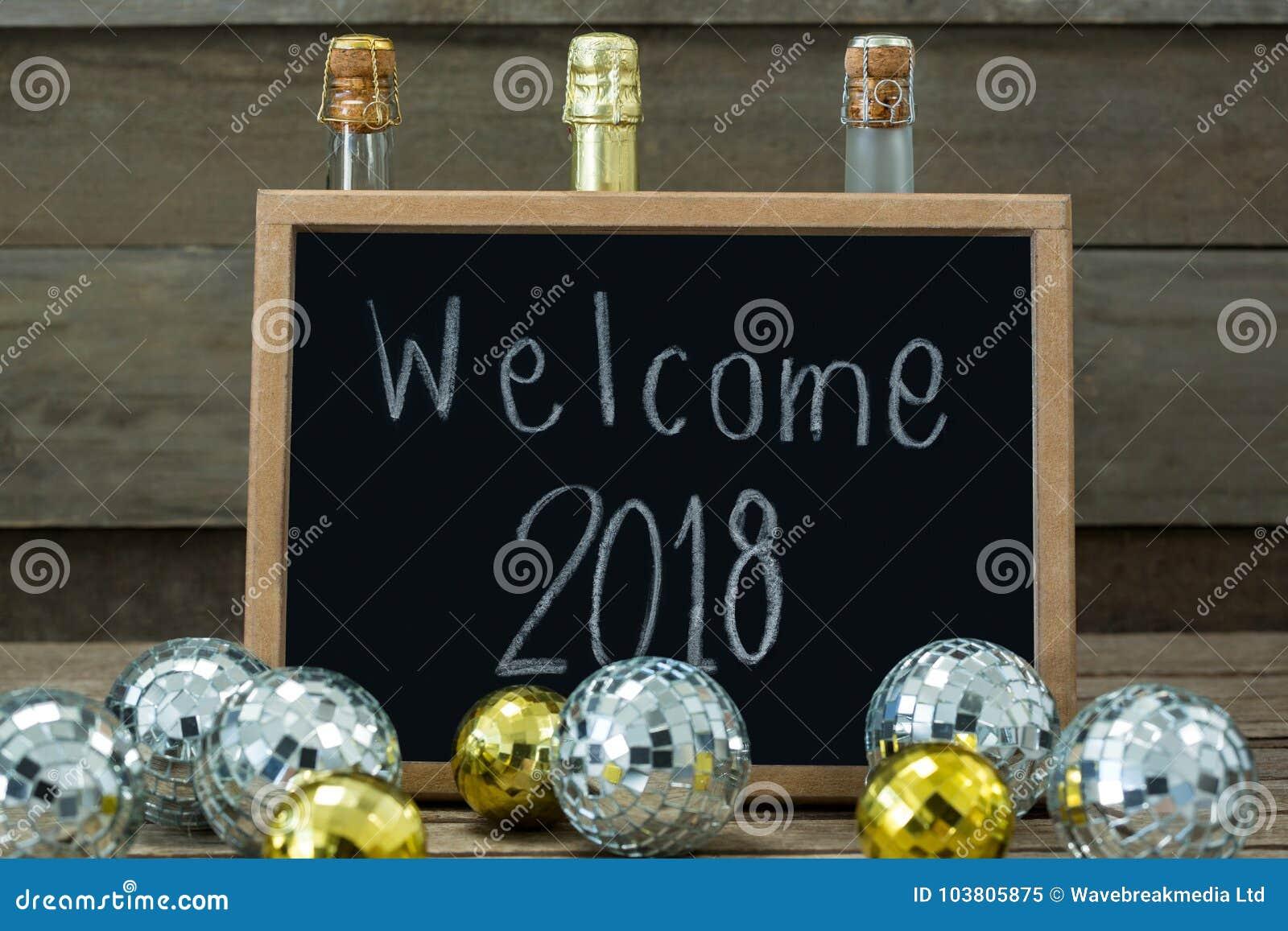Dé la bienvenida a 2018 escrito en tablero de la pizarra con las chucherías y la botella del champán