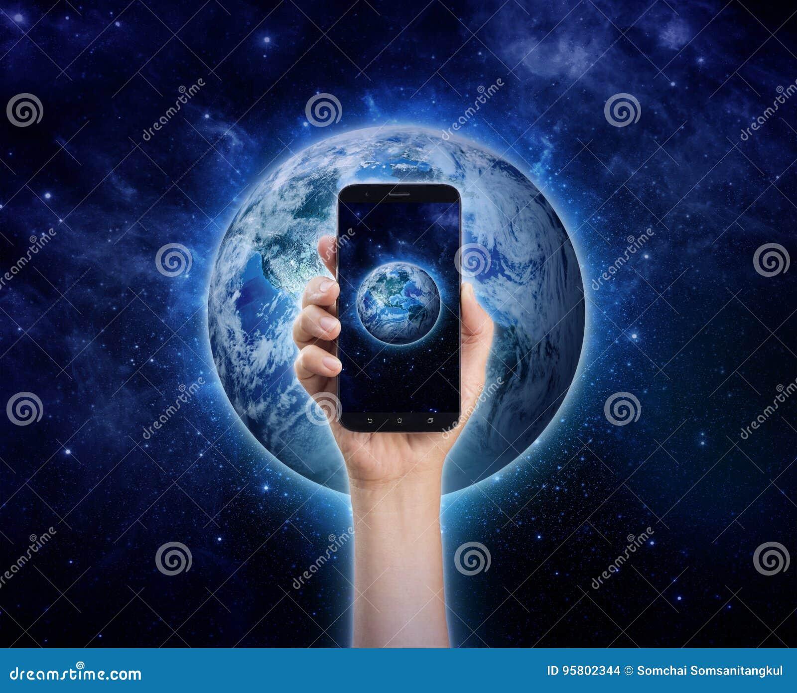 Dé sostener el teléfono móvil o el teléfono elegante en backgro de la tierra del planeta