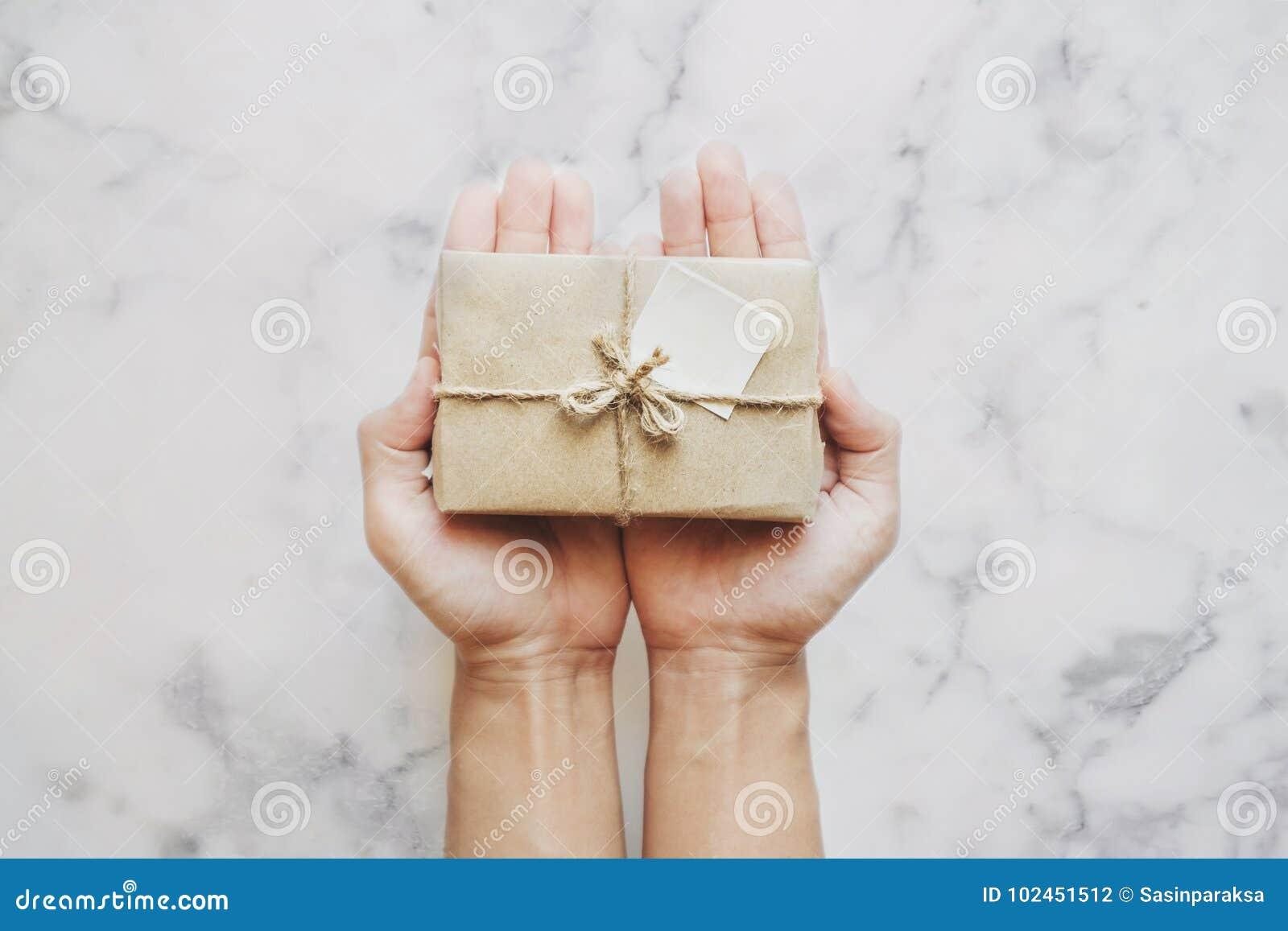 Dé sostener la caja de regalo del paquete, en el fondo de piedra de mármol blanco de la tabla