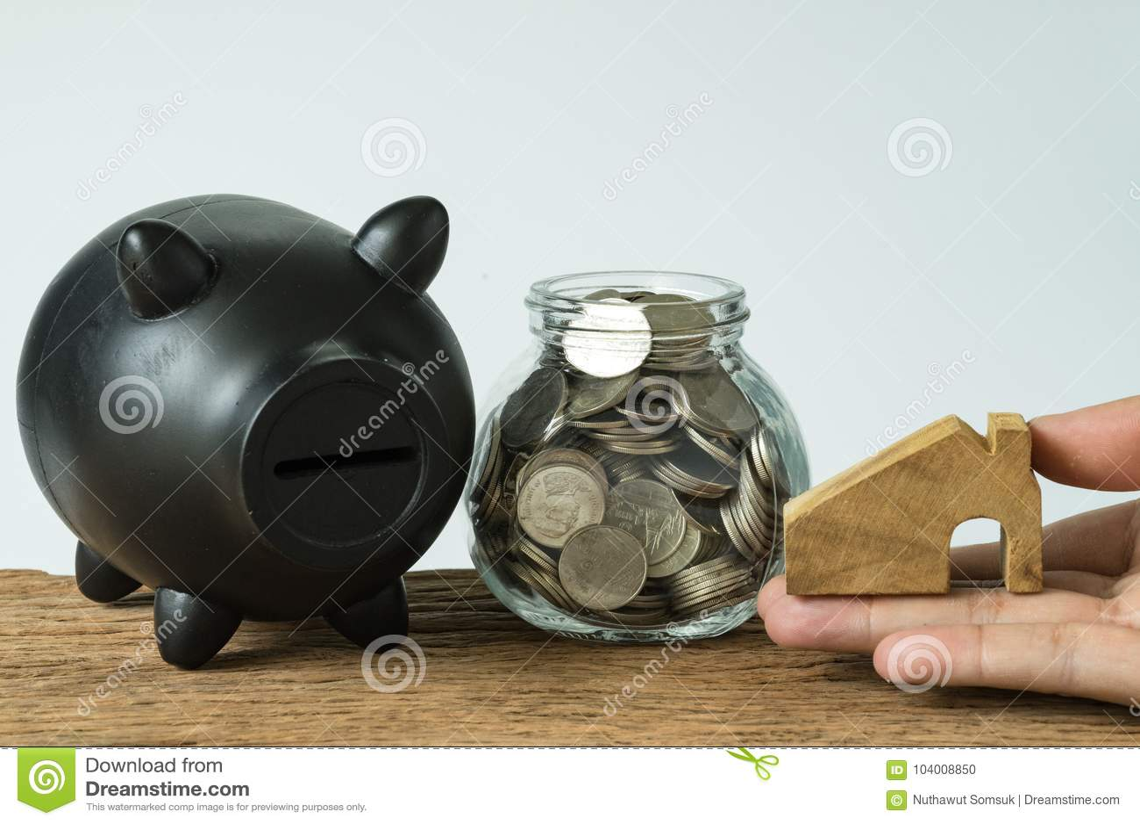 Dé sostener la casa miniatura de madera con las monedas en tarro y negro