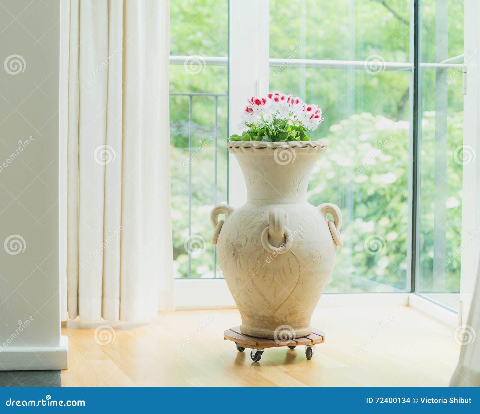 Décoration à la maison avec l amphore ou le vase à terre cuite avec des fleurs