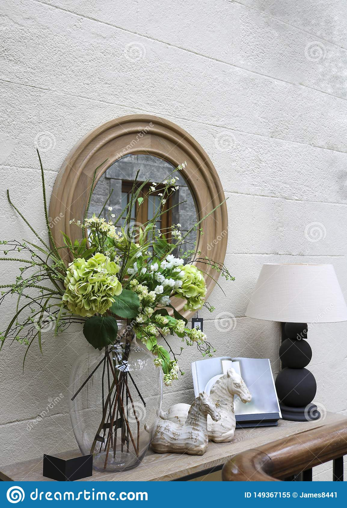 D?coration d?corative de mur : un miroir, une console avec une lampe, fleurs et bibelots