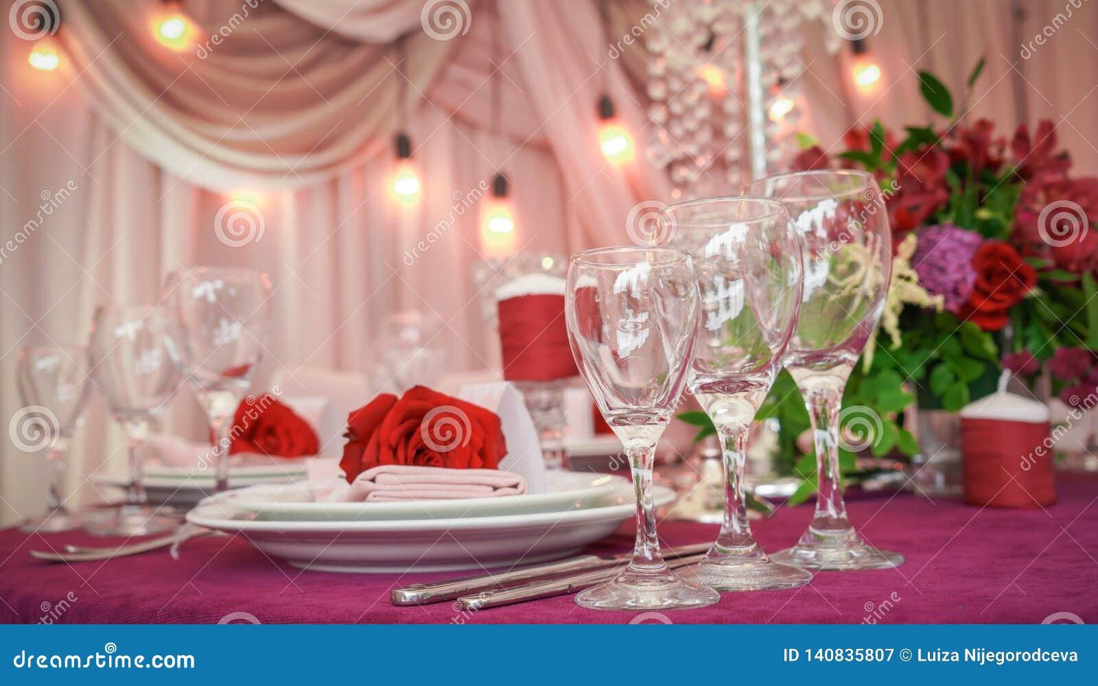 Décoration de fête de table avec les fleurs et les verres rouges