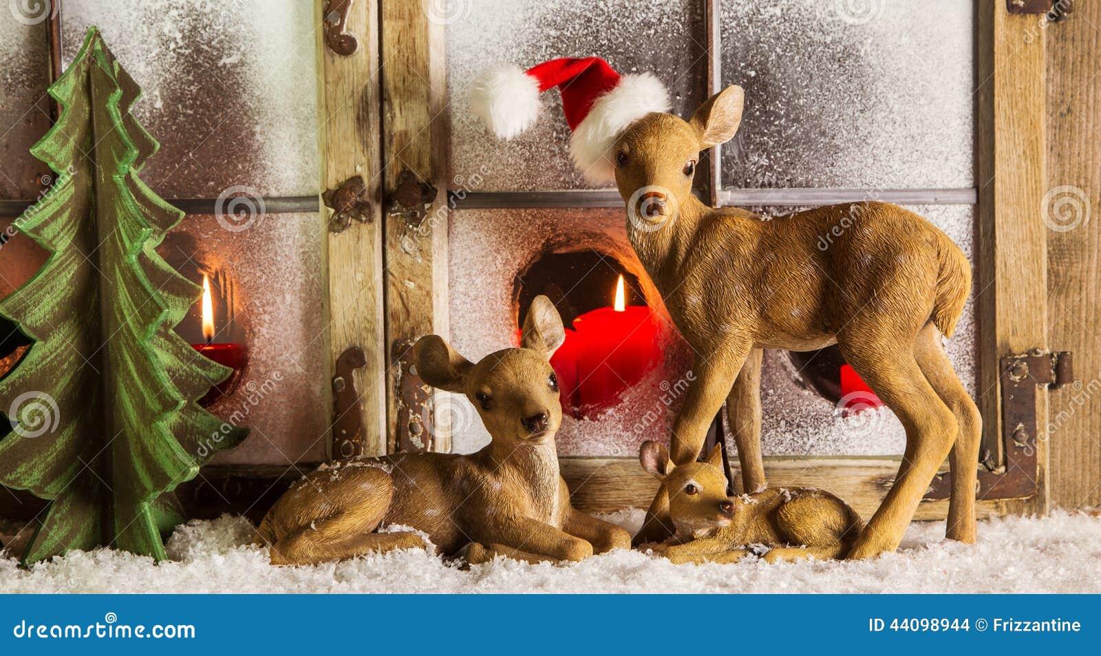 Décoration de fenêtre de Noël : famille de cerfs communs avec les bougies rouges