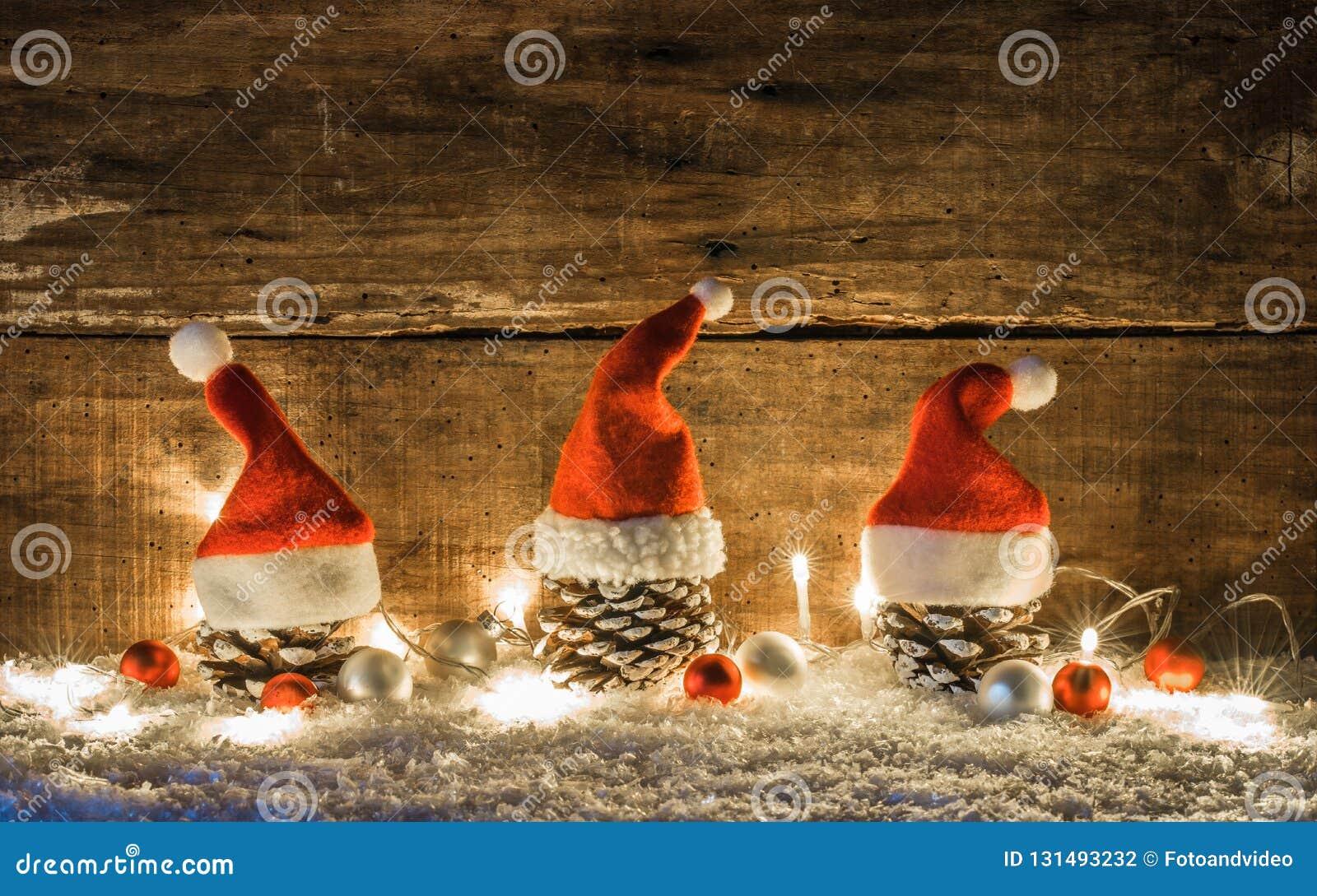 Décoration de Noël avec des cônes de pin décorés des chapeaux rouges du père noël au-dessus de la neige avec la lumière et les or