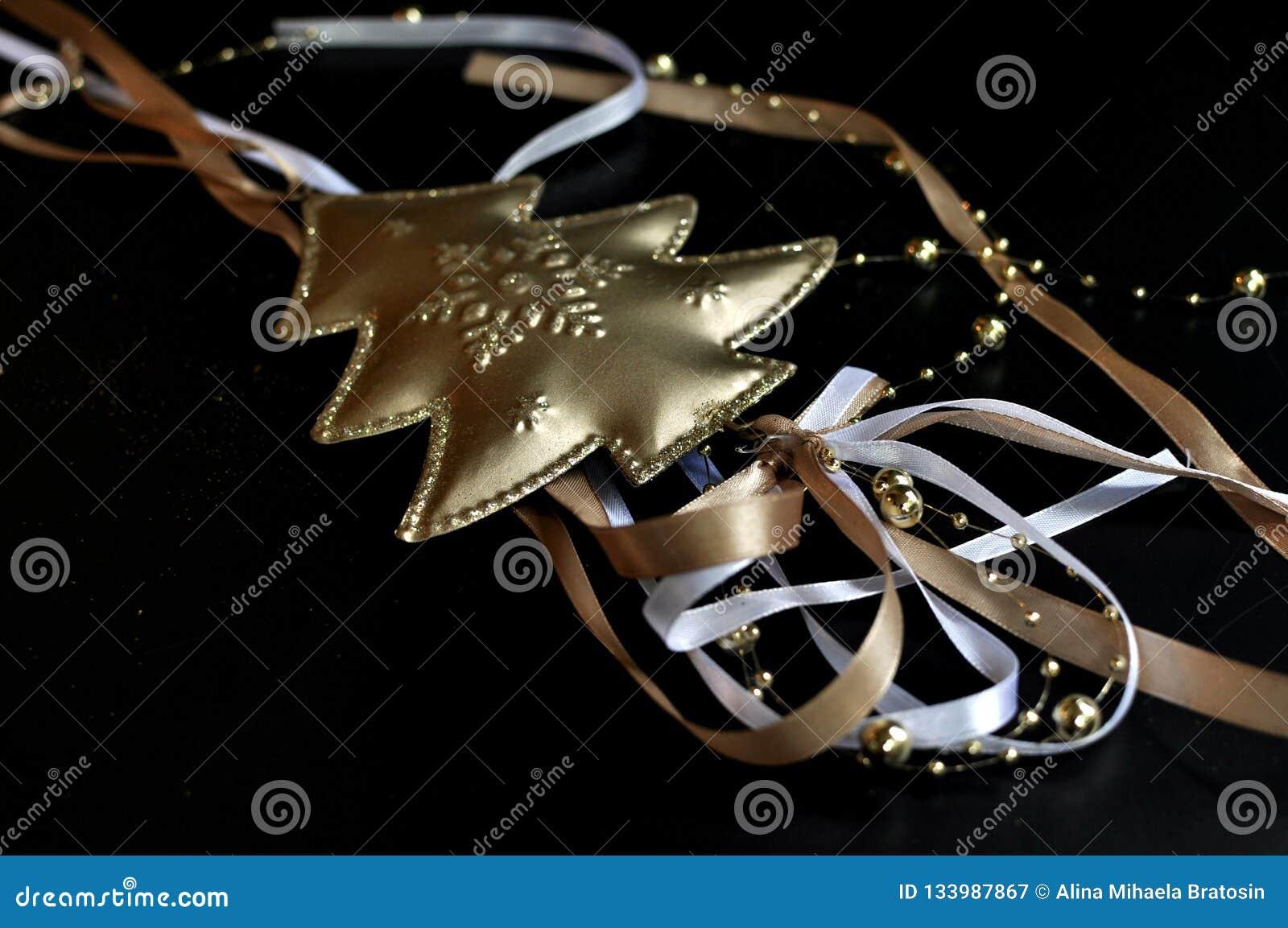 Décoration de Noël représentant un arbre d or avec le laçage coloré sur le fond noir