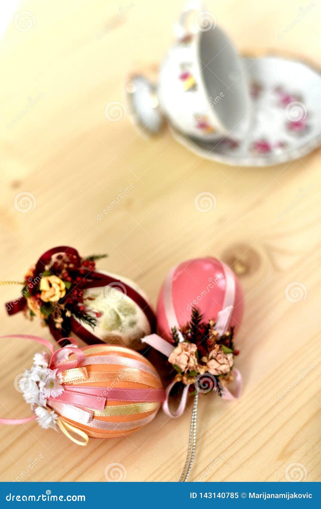 Décoration de Pâques de cru de trois oeufs de pâques colorés roses brillants décorés des rubans et de la tasse et soucoupe de cru