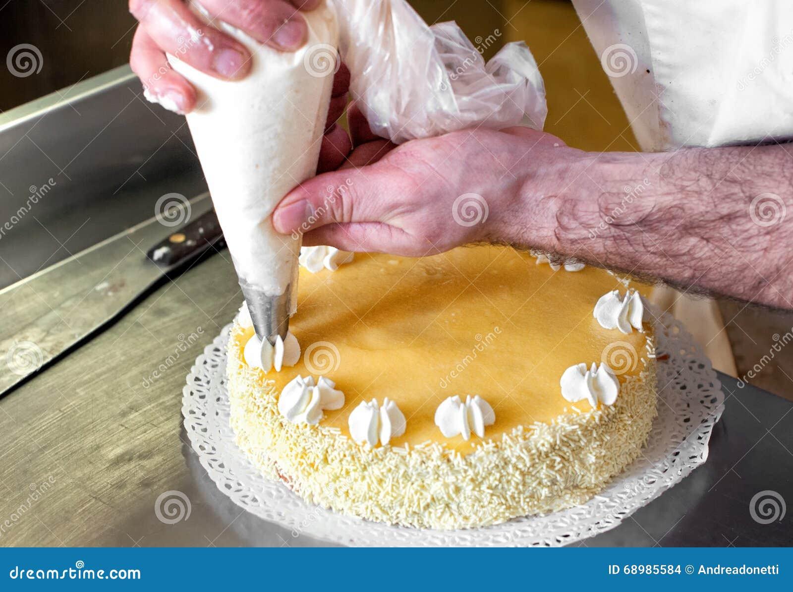 Décorations crèmes sifflantes de Baker sur un gâteau