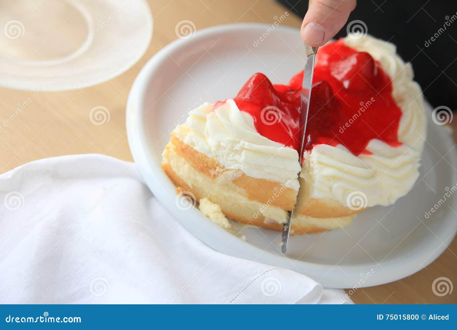 Découpage en tranches d un gâteau avec le lustre fouetté de crème et de fruit