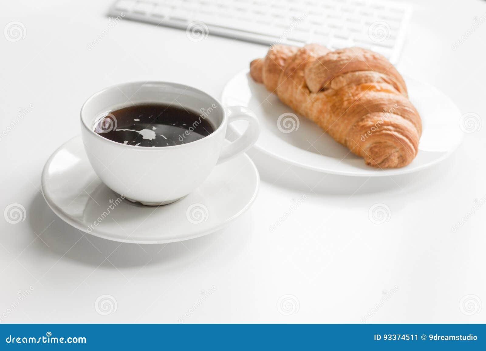 Déjeuner de bureau avec du café et le croissant clavier sur le