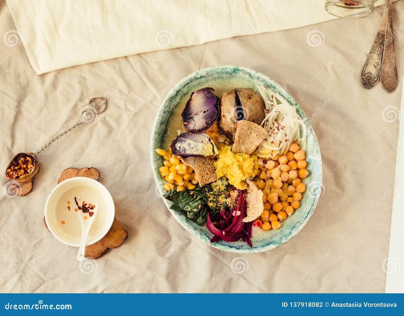 Déjeuner de Detox avec une pomme de terre pourpre, des épinards cuits, et un houmous avec des biscuits de maïs