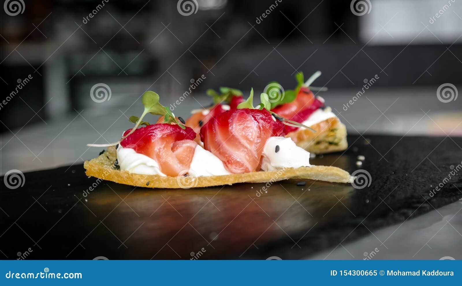 Délicieux amusez l apéritif de bouche, les saumons traités avec des betteraves, les échecs et la fleur orange - nourritures luxue