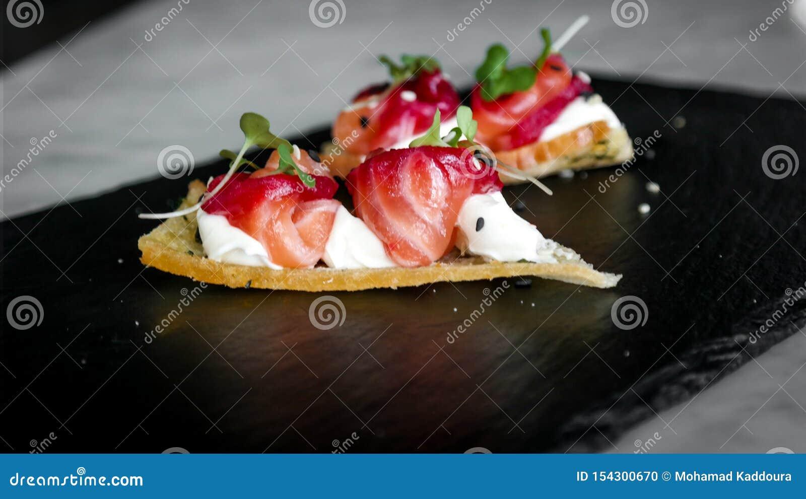 Délicieux amusez l apéritif de bouche, les saumons traités avec des betteraves, le fromage et la fleur orange - nourritures luxue