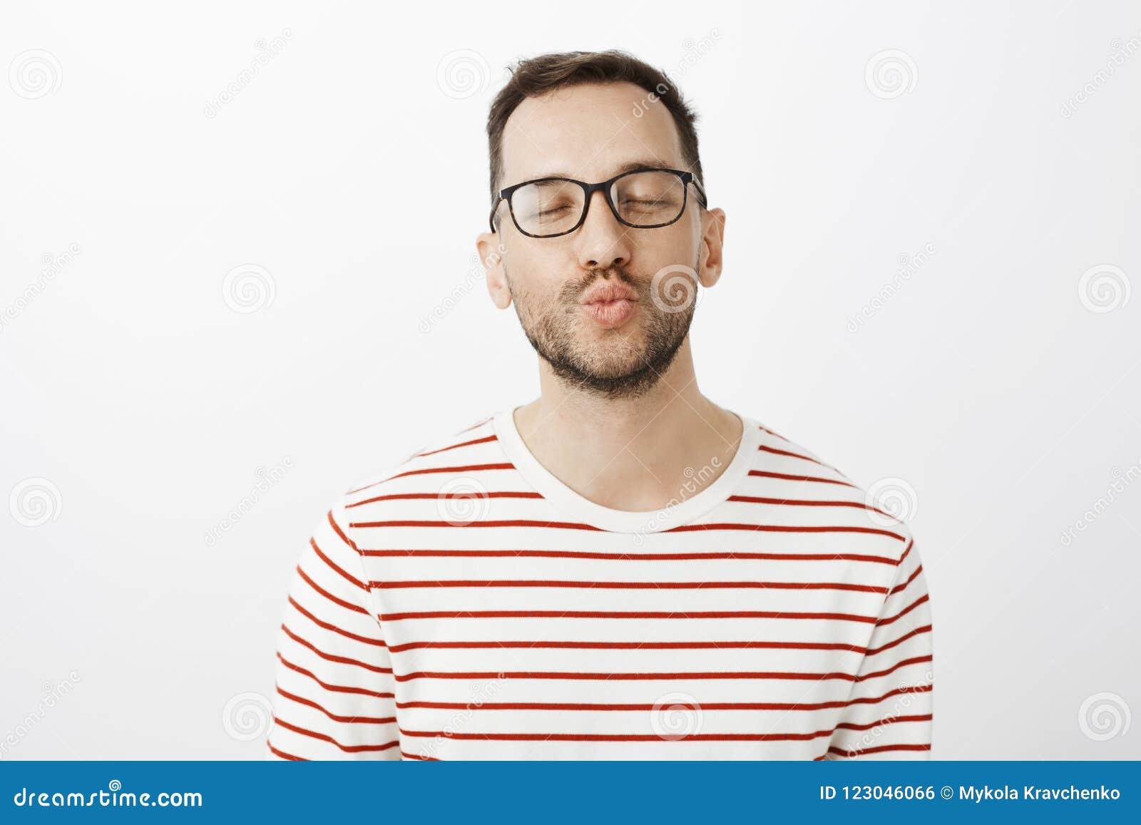 Déme el mwah El novio atractivo sensual contento en vidrios elegantes negros, labios plegables y el closing observa con el sligh