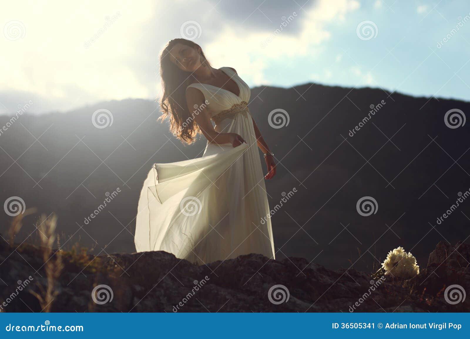 Dépassement léger de coucher du soleil par la robe de jeune mariée