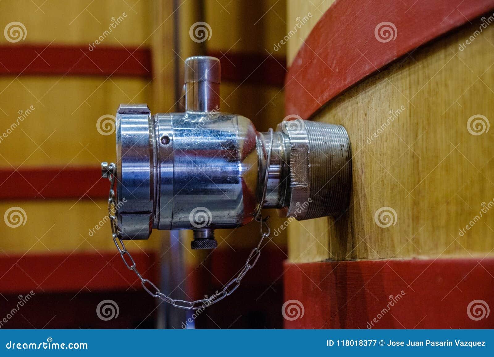 Détail d un robinet en métal pour vider un grand baril où les raisins commencent à fermenter pour devenir vin