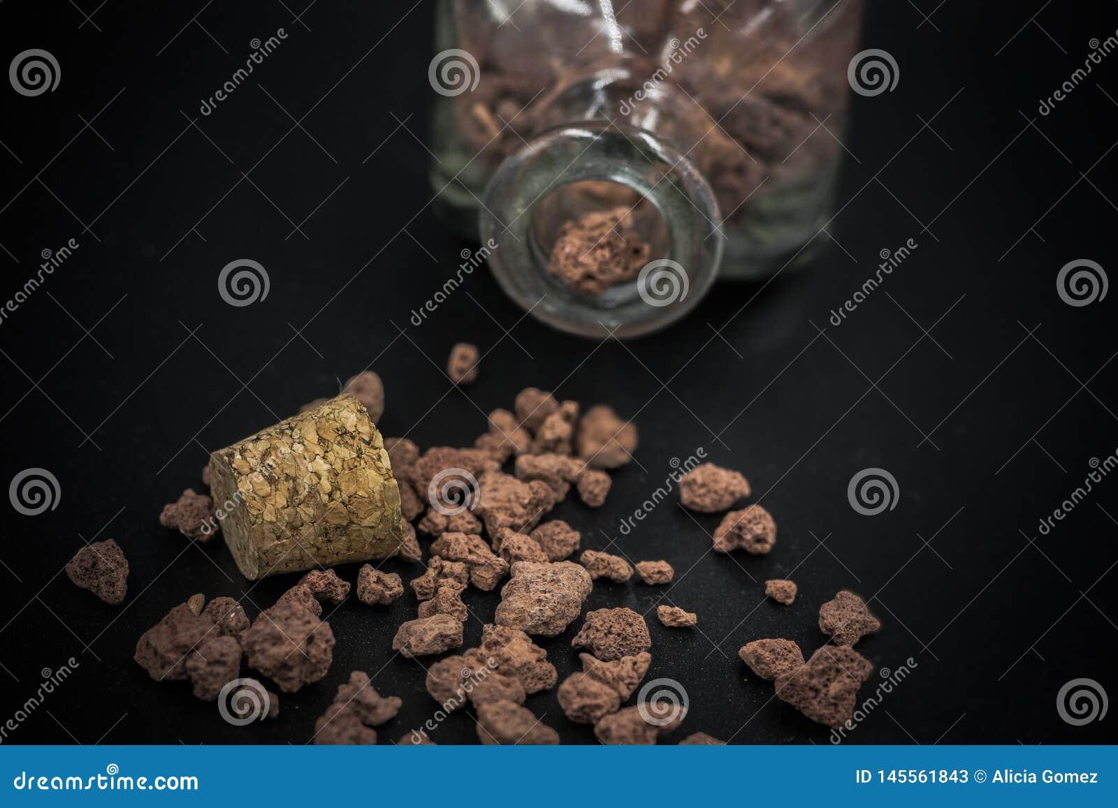 Détail de la bouteille en verre avec des pierres à l intérieur et dispersé sur le plancher