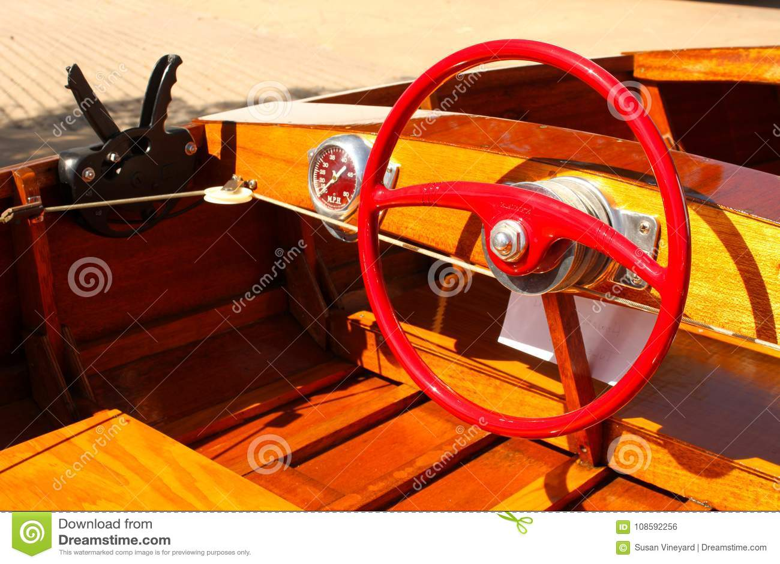 Détail du bateau en bois de vitesse avec le volant rouge lumineux au dock avec les vitesses et le tachymètre