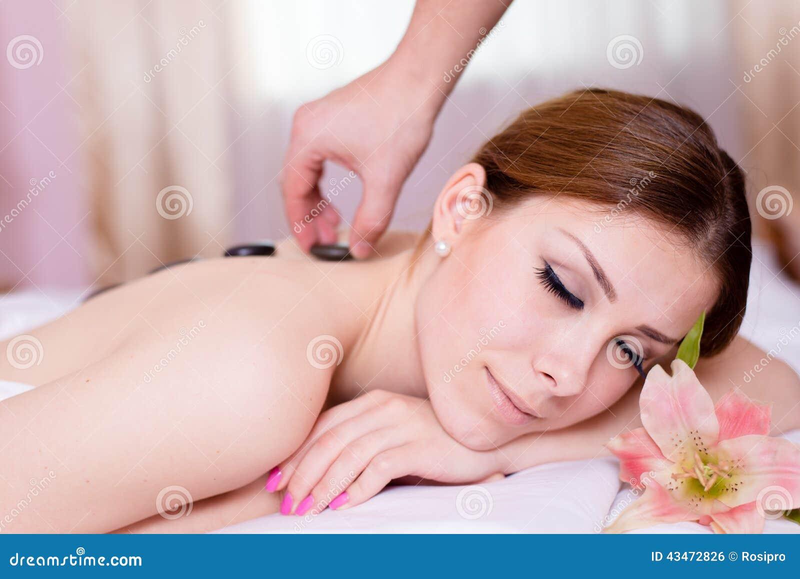 Détente de station thermale : belle jeune dame blonde ayant l amusement appréciant la relaxation pendant le massage en pierre et