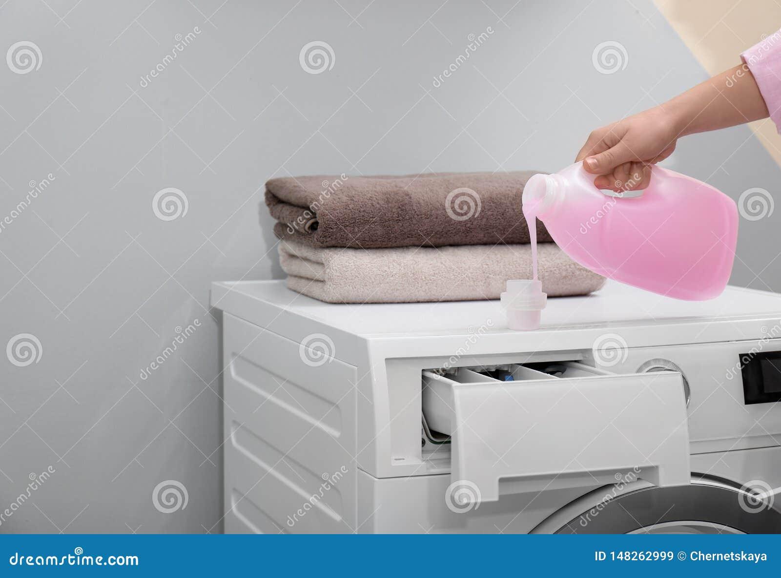 D?tergent de blanchisserie de versement de femme dans le chapeau sur la machine ? laver ? l int?rieur, plan rapproch?
