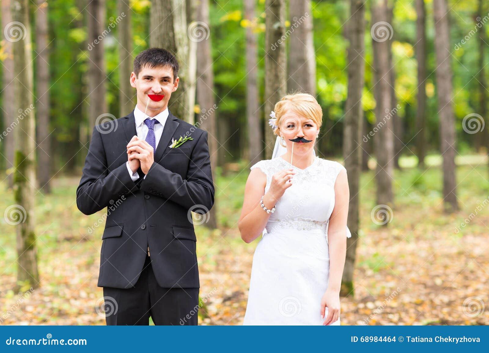 Día de April Fools   Pares que presentan con los labios del palillo, máscara de la boda
