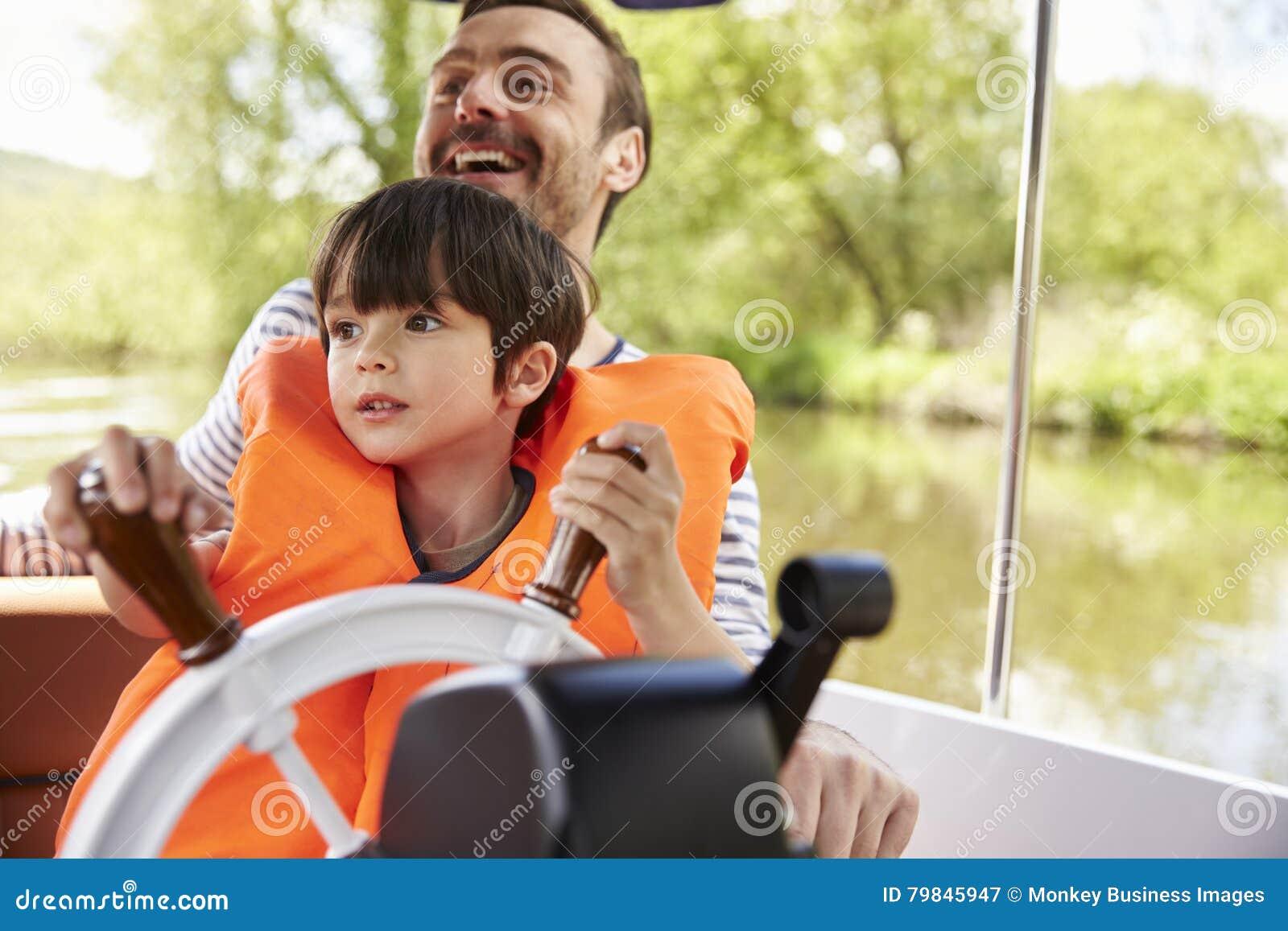 Día de And Son Enjoying del padre hacia fuera en barco en el río junto