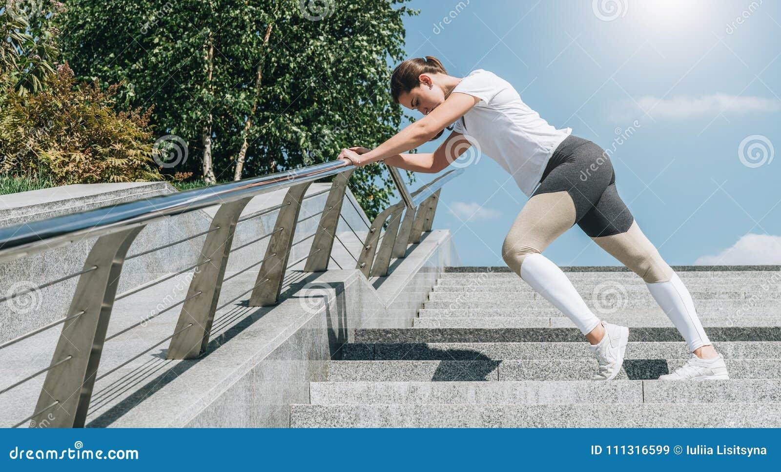 Día de verano asoleado Mujer joven que hace estirando los ejercicios al aire libre Muchacha que hace calentamiento en pasos antes