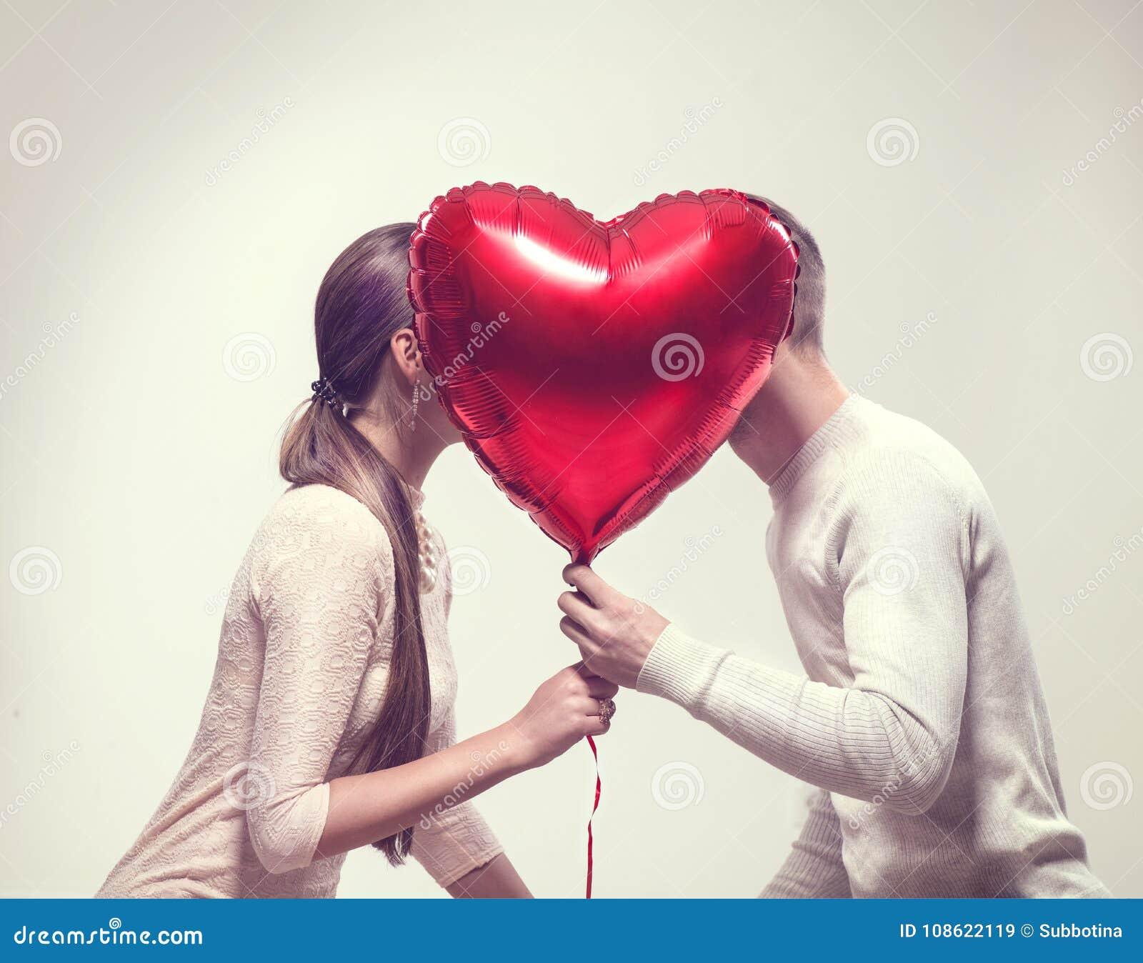 Día del `s de la tarjeta del día de San Valentín Pares alegres felices que celebran el balón y besarse de aire en forma de corazó