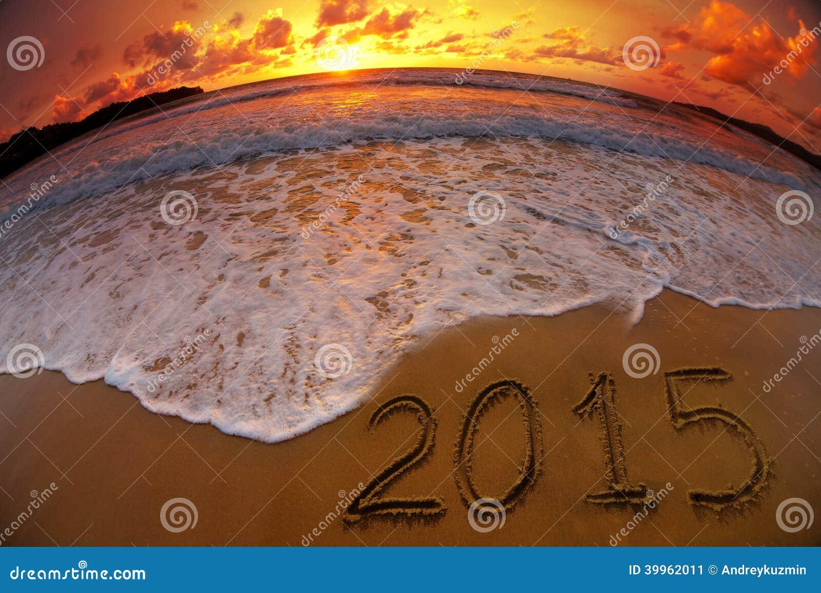 Dígitos do ano 2015 no por do sol da praia do oceano