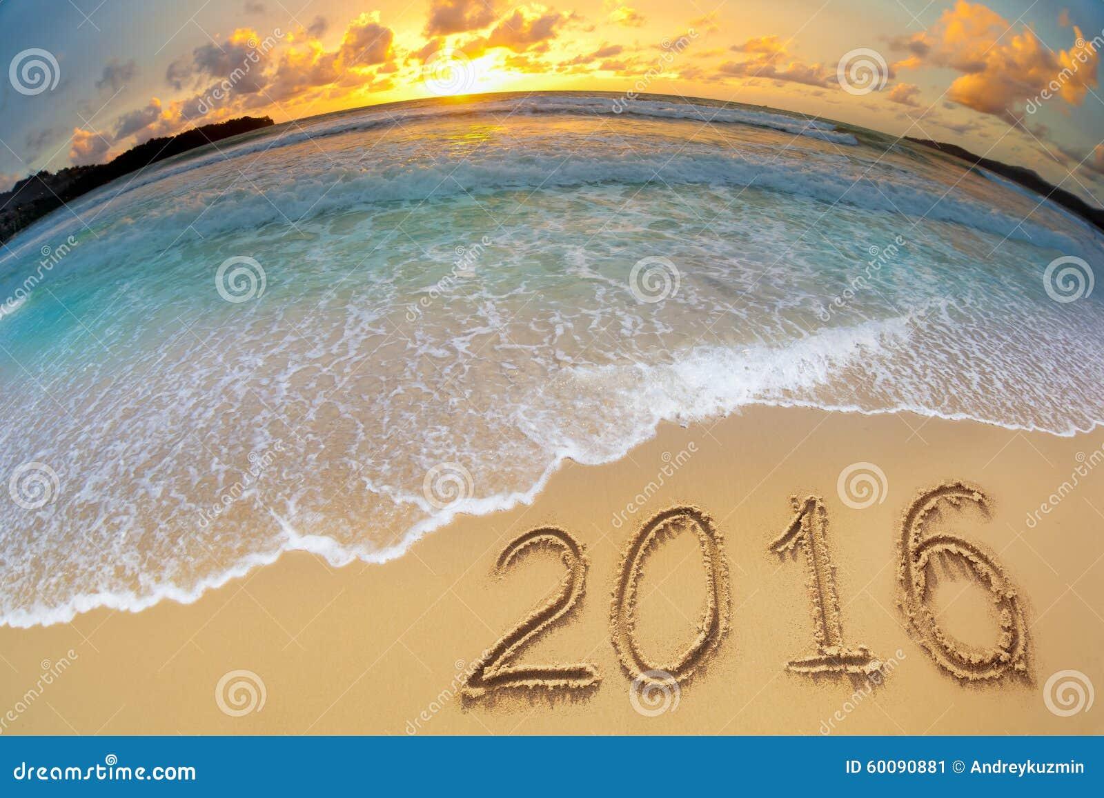2016 dígitos do ano novo escritos na areia da praia