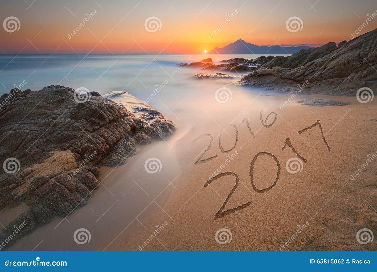 Dígitos 2016 e 2017 na areia da costa no nascer do sol