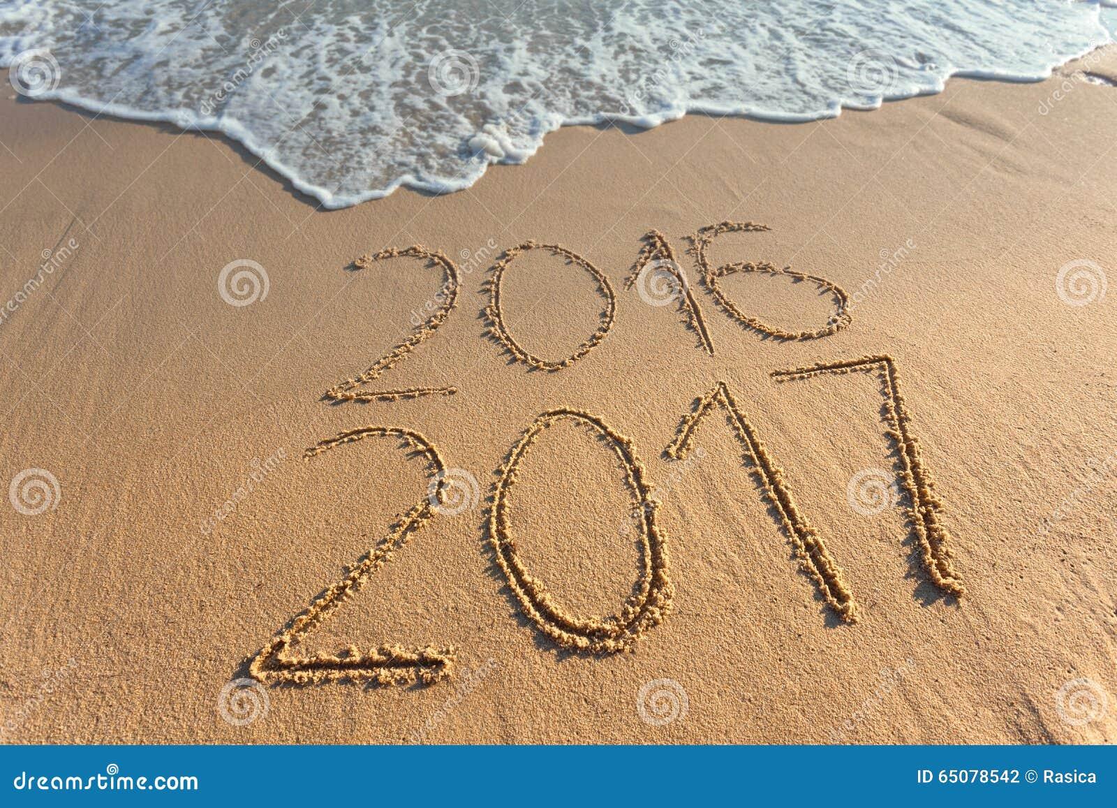 Dígitos 2017 e 2016 na areia da costa no por do sol