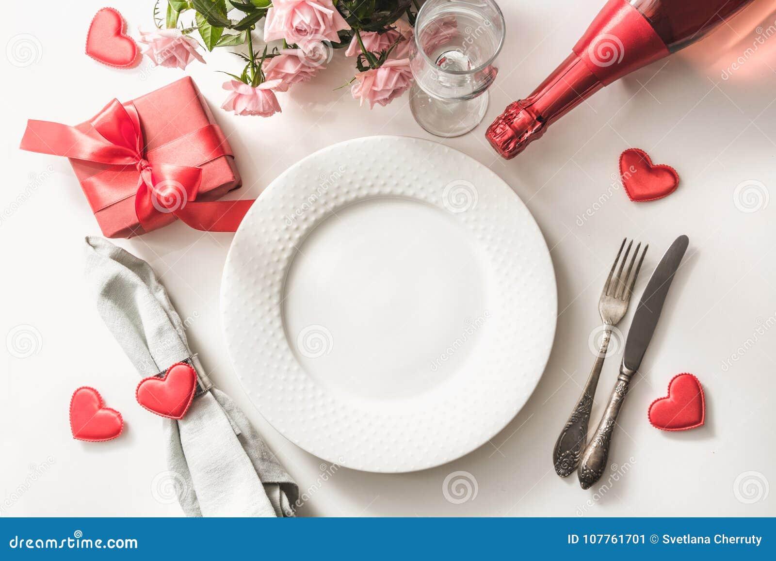 Dîner de jour de valentines avec le couvert de table avec le cadeau rouge, verre pour le champagne, une bouteille de champagne, r