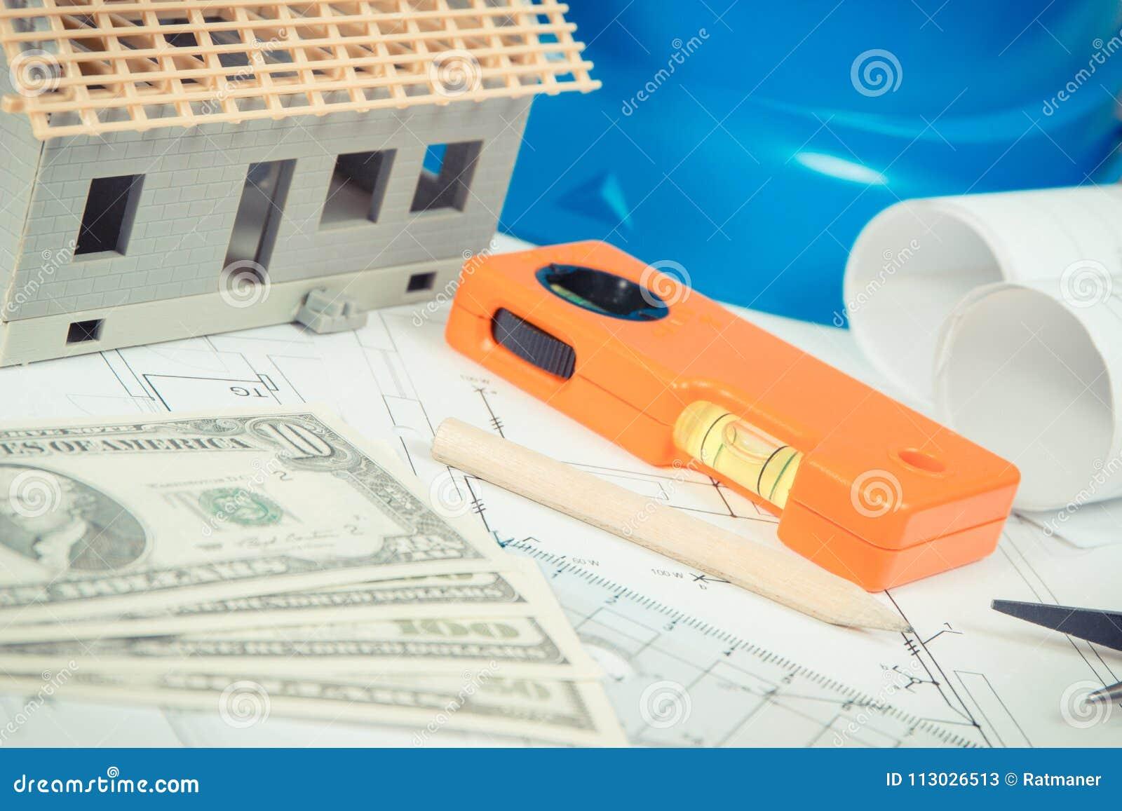 Dólar, diagramas eléctricos, herramientas del trabajo y accesorios y casa bajo construcción