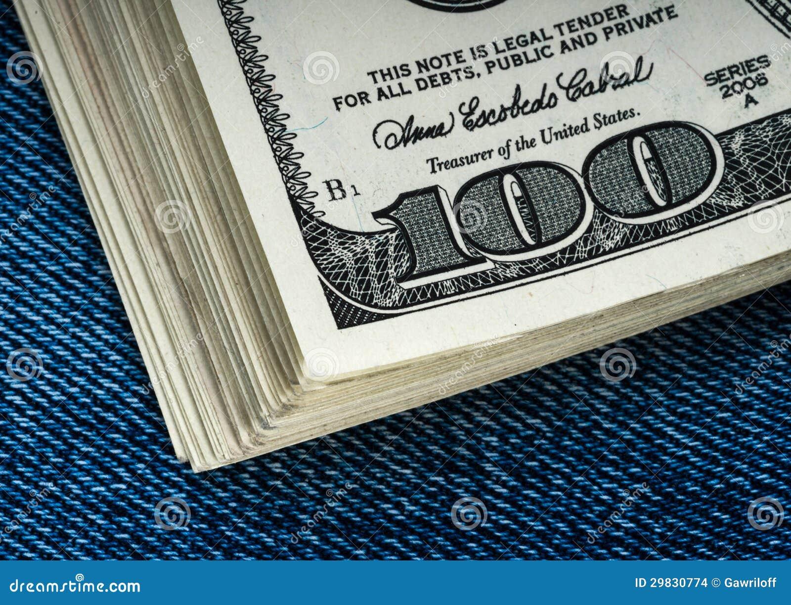 Dólares em um bolso das calças de brim
