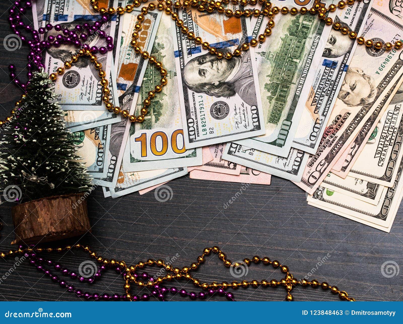 Dólares do dinheiro que coloca em ramos de árvore do abeto do Natal no fundo queimado da superfície da placa de madeira Decoraçõe