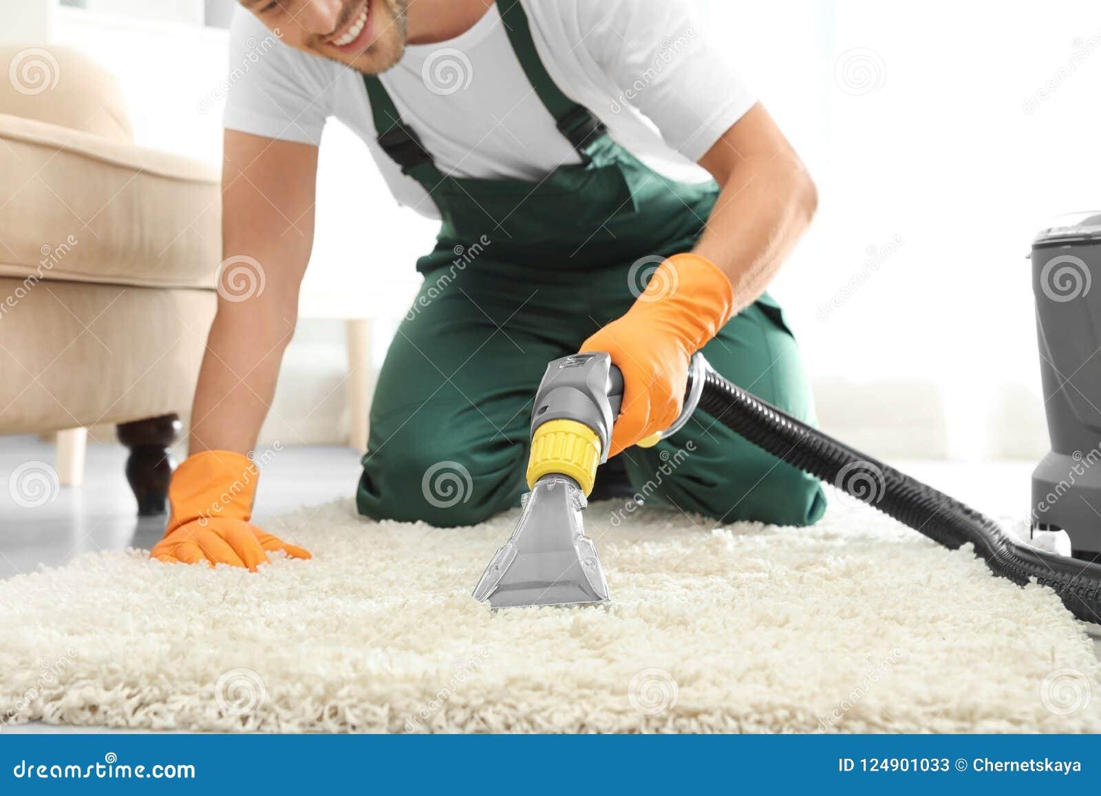 Dörrvakt som inomhus tar bort smuts från filten med mattrengöringsmedlet