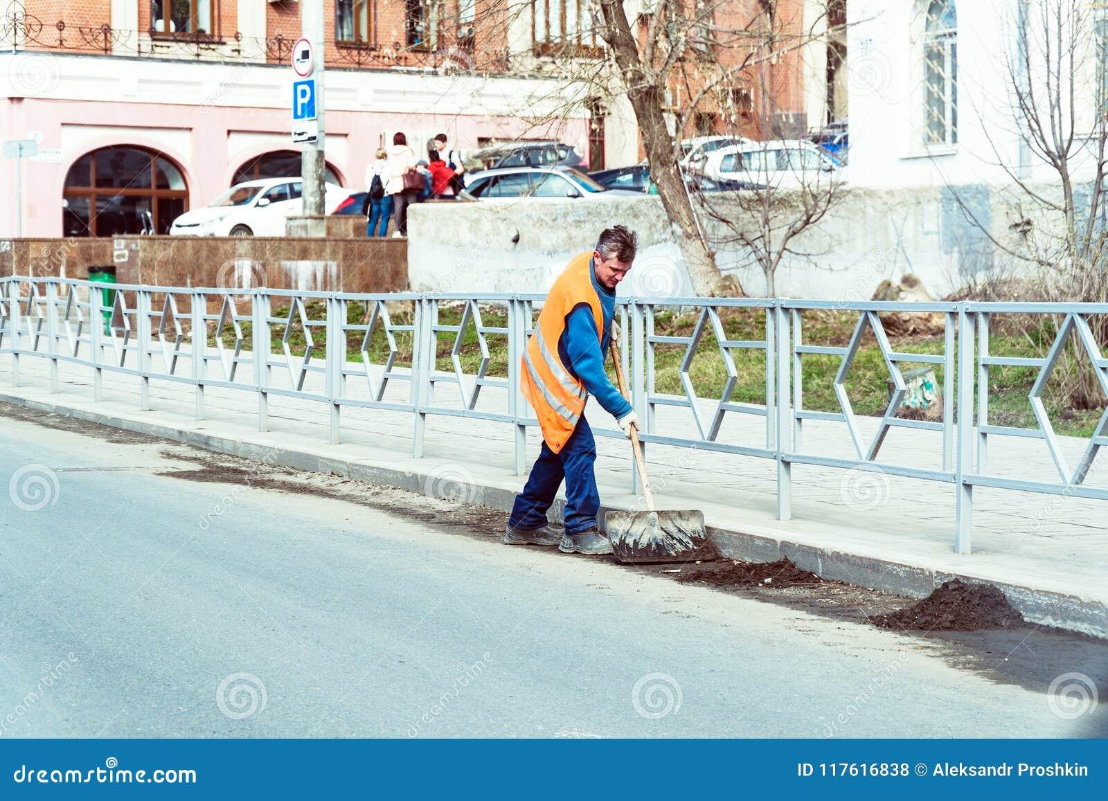 Dörrvakten i en apelsinlikformig gör ren avskrädet med en skyffel på stadsgatan