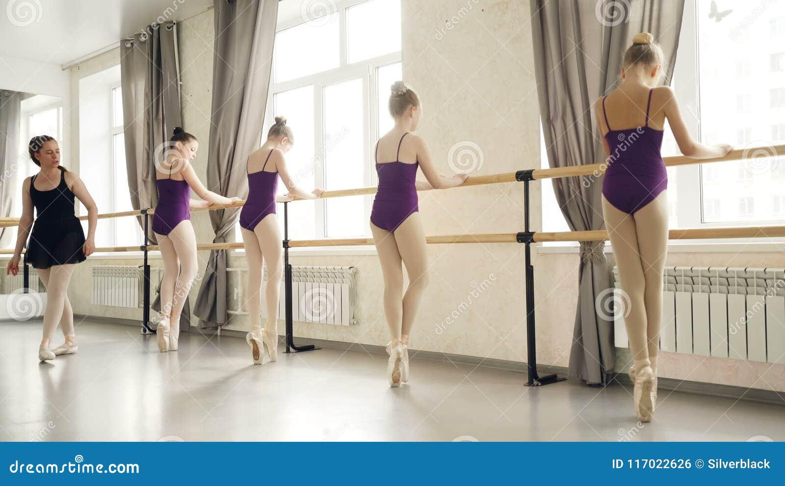 Dünne Mädchen in den Trikotanzügen und in den Ballettpantoffeln tun plie und an gehend gehen auf den Zehen Ballett Barre während.