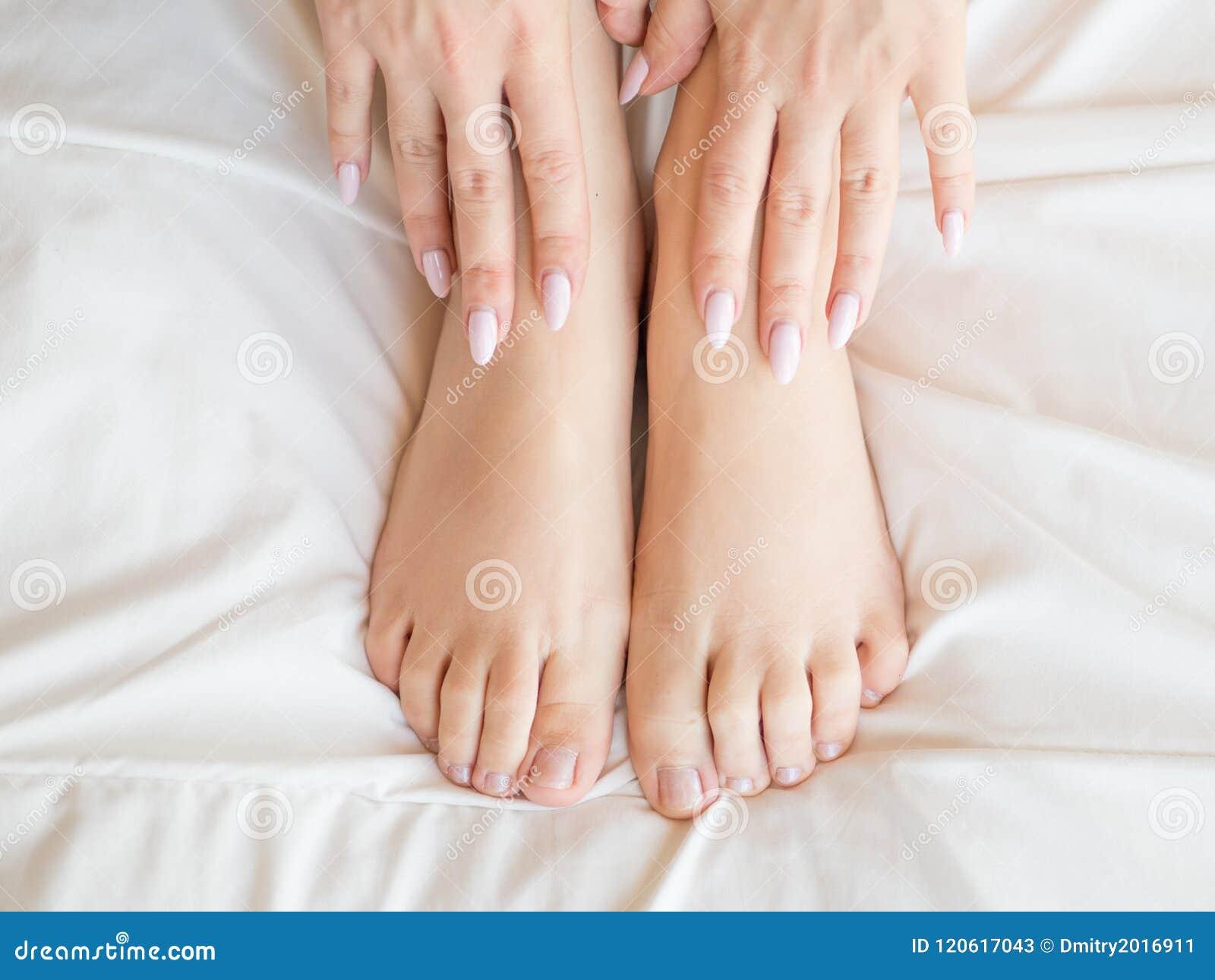 Dünne, perfekte und schöne gekreuzte Frauenbeine auf Bett Geerntetes Bild von auf Bettschönheit erotisch herein liegen