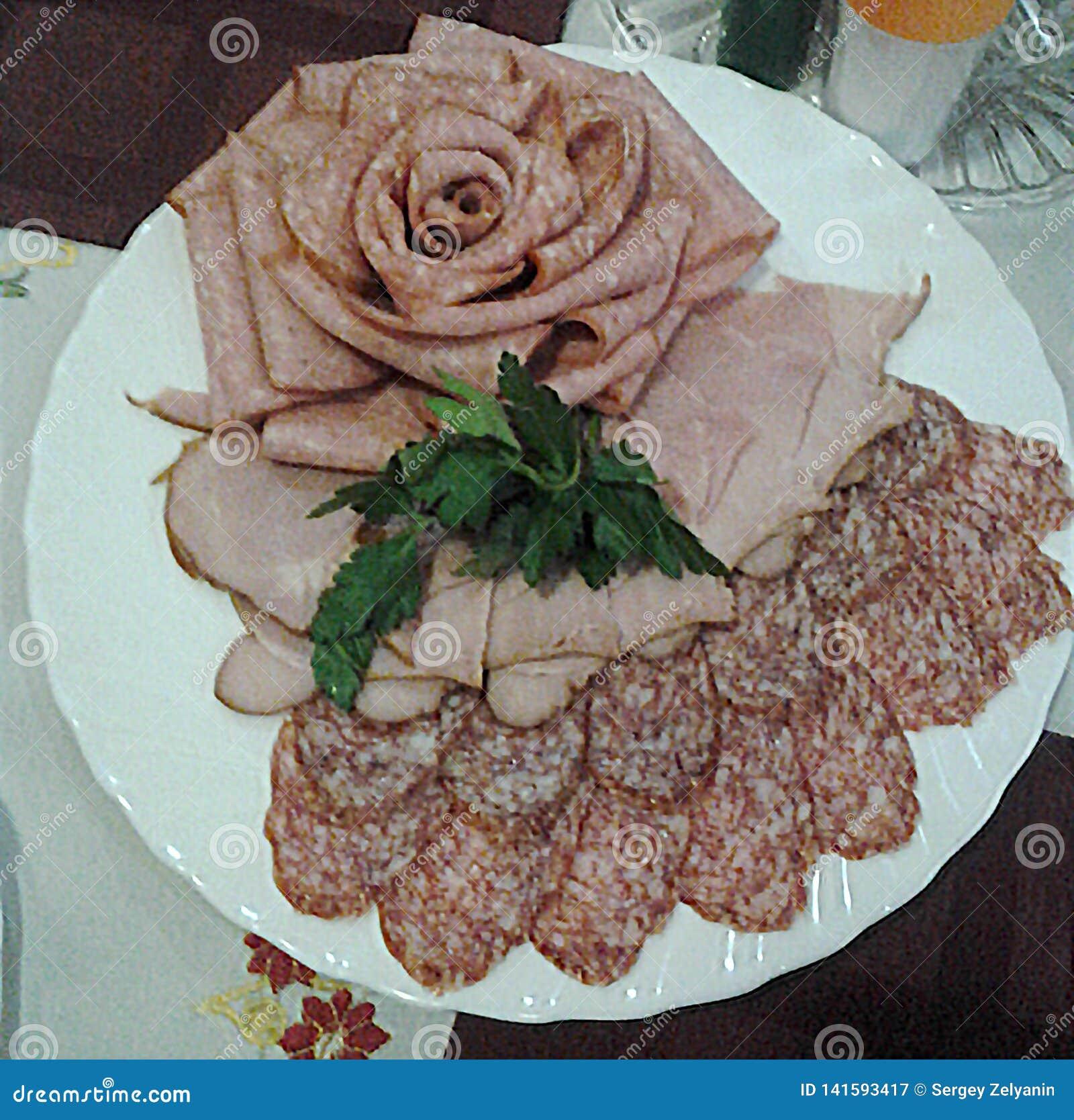 Dünner Ausschnitt des Fleisches und der geräucherten Wurst, verziert mit Grüns