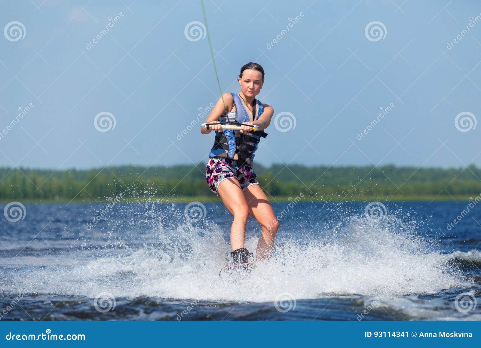 Dünnes Frauenreiten-wakeboard auf Welle des Bootes