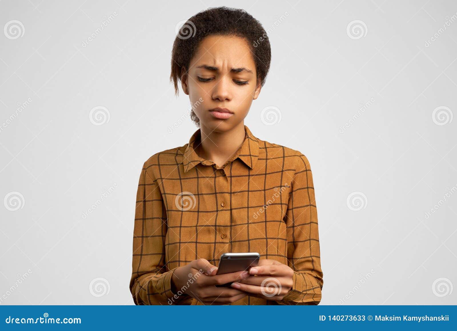 Düsteres umgekipptes Mädchen macht Grimasse von der Verzweiflung, hält Smartphone, liest disapponting Nachrichten, die entmutigte