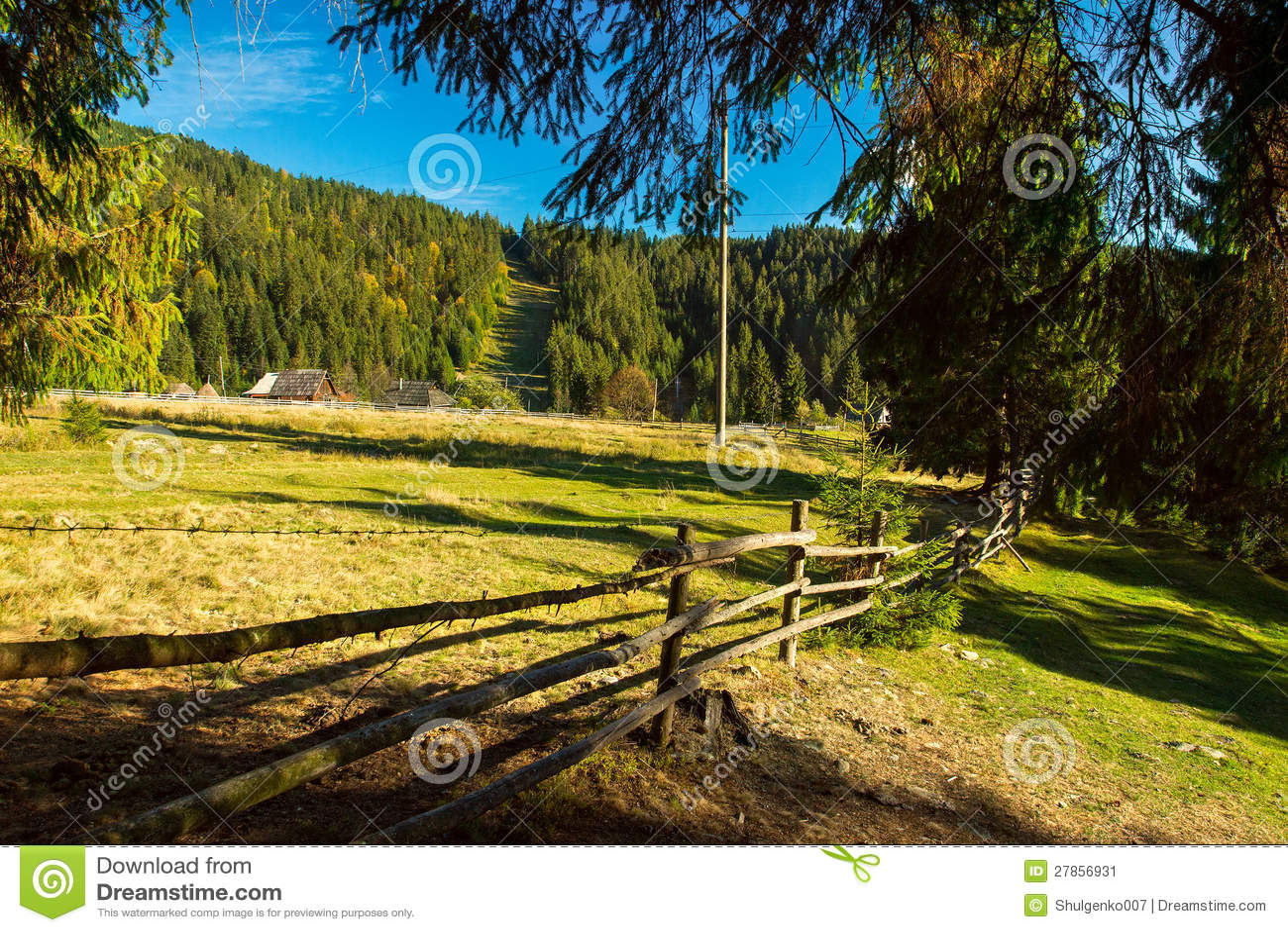 Długi drewniany ogrodzenie wzdłuż Karpackich łąk