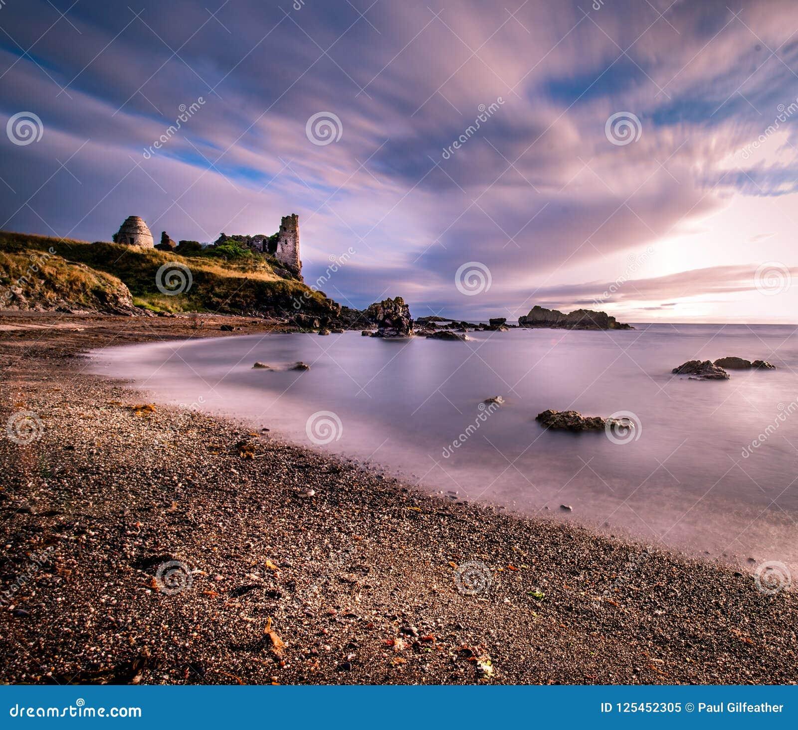 Długi ujawnienie uwypukla stare rocznik ruiny Dunure kasztel z wispy seascape gładzi chmury i ocean
