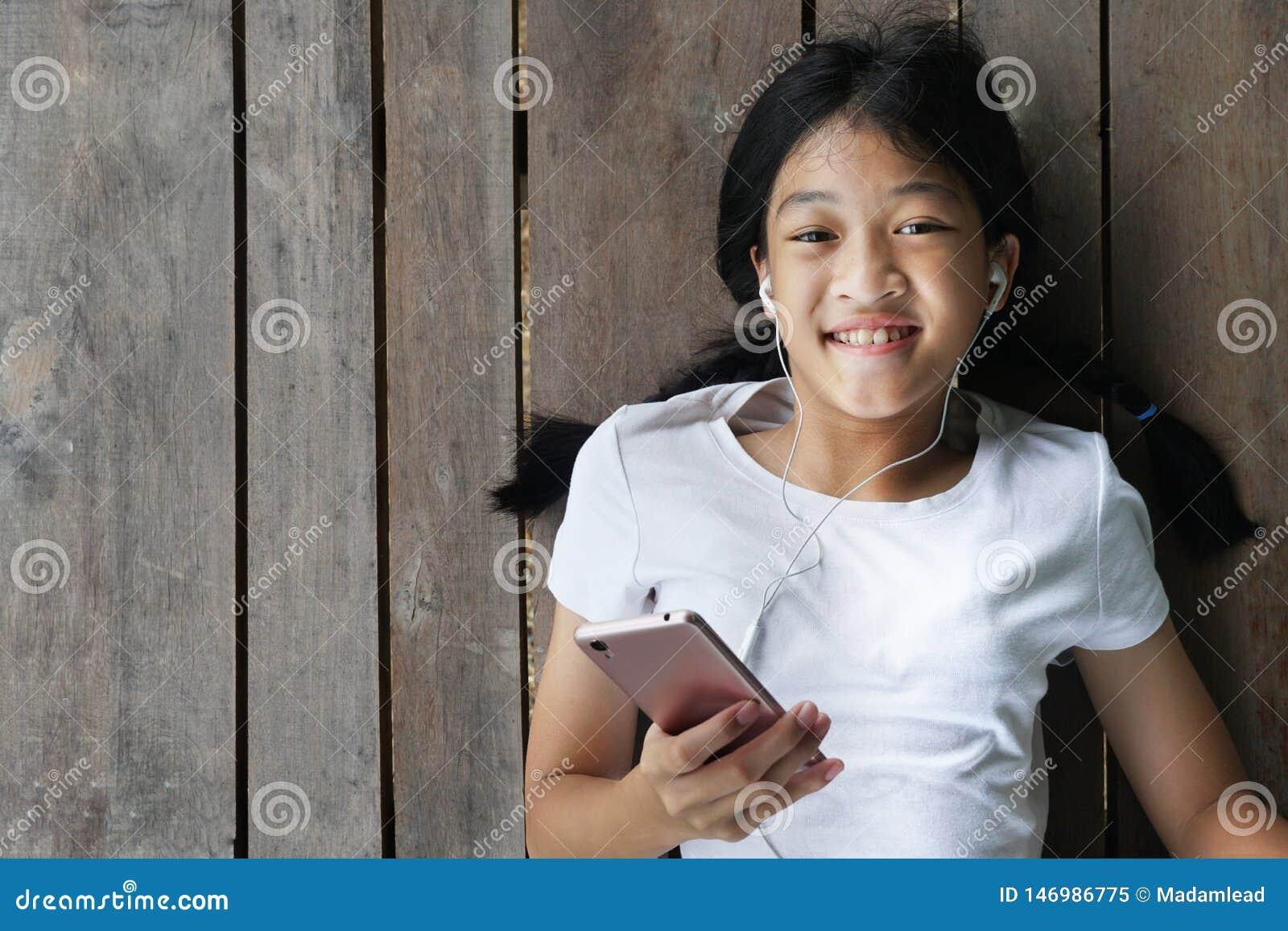 Długie włosy dzieciak dziewczyna z białą koszulką z mobilnym mądrze telefonem słucha muzyka białą słuchawką kłaść puszek dalej