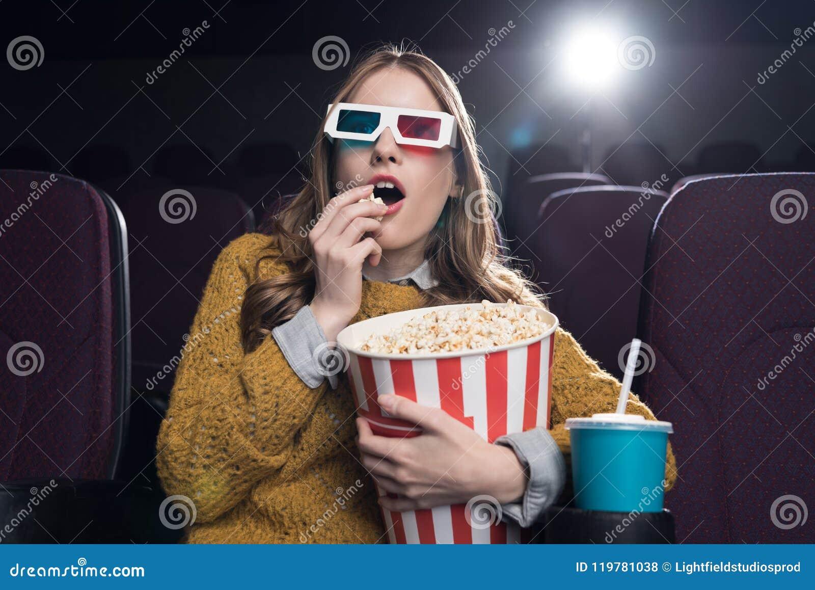 3d玻璃的激动的妇女吃玉米花和观看电影的